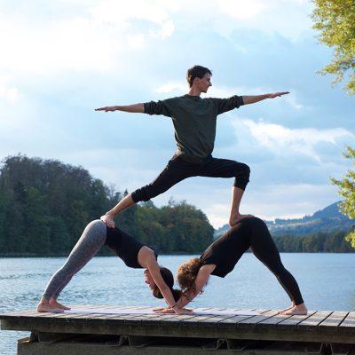 Acrobatic Yoga Facing Dog Pyramid Pose mit Warrior