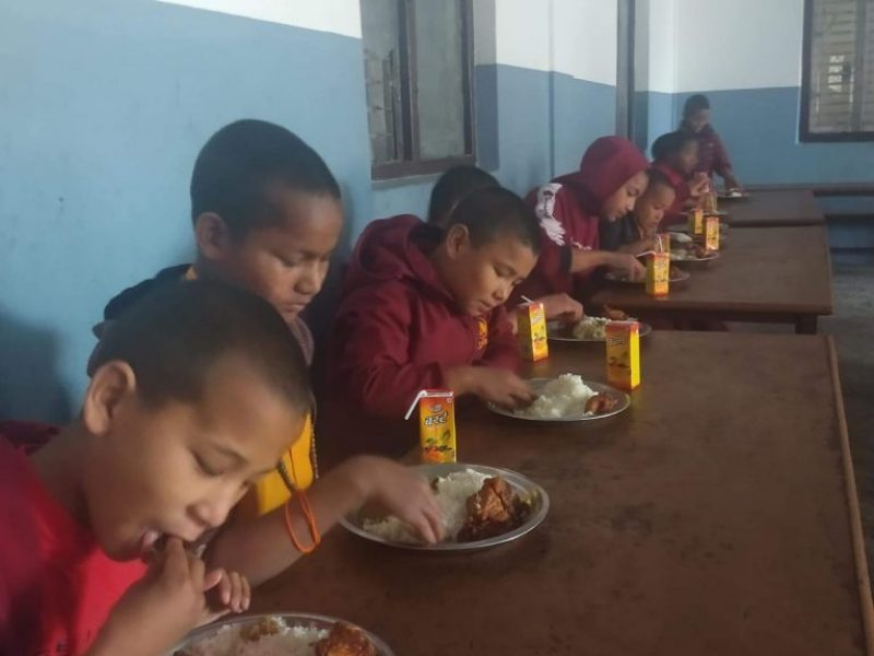 Sie sehen Schulkinder des Klosters beim Essen.